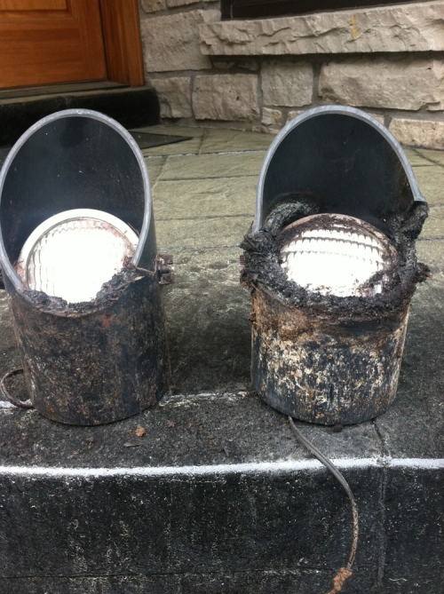 Damage beyond belief- these well lights were melted and destroyed from being filled with mulch by this homeowners landscaper